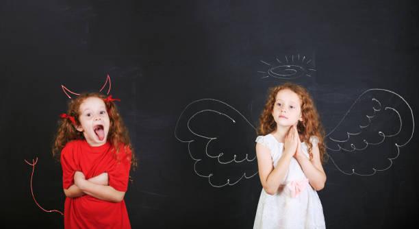 Böse Mädchen Imp Hörnern und Schwanz und ein Engel Mädchen – Foto