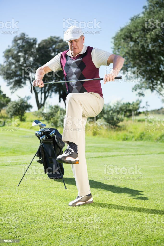 Angry golfer trying to break his club stock photo