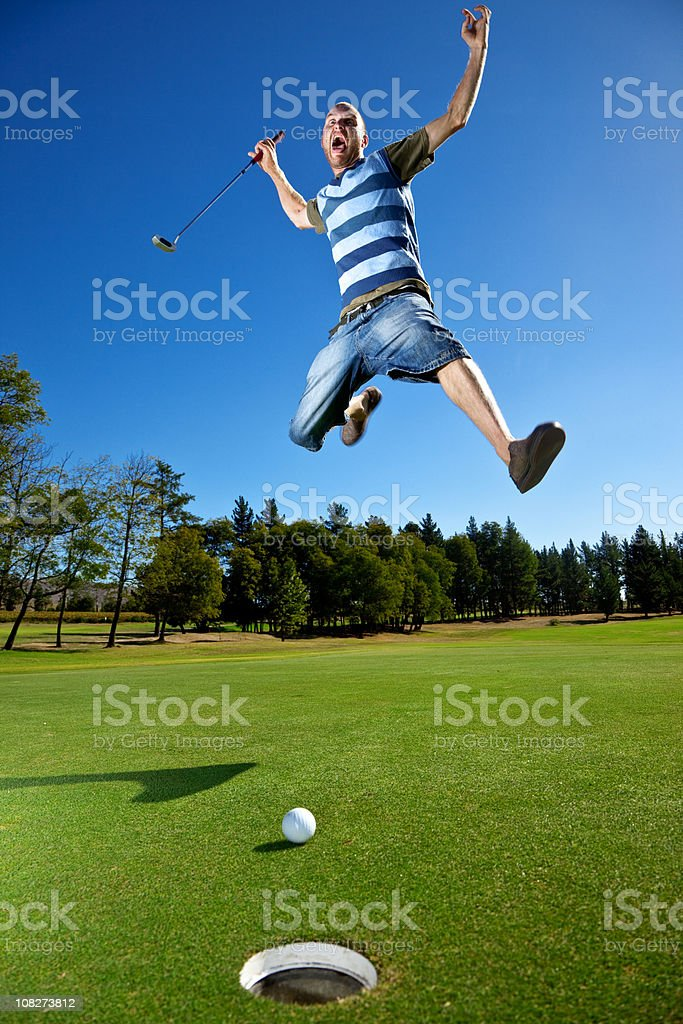 Angry Golfer Yelling and Jumping on Golf Green Near Hole stock photo