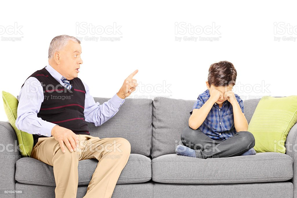 Angry grandad shouting at his nephew, seated on a sofa stock photo