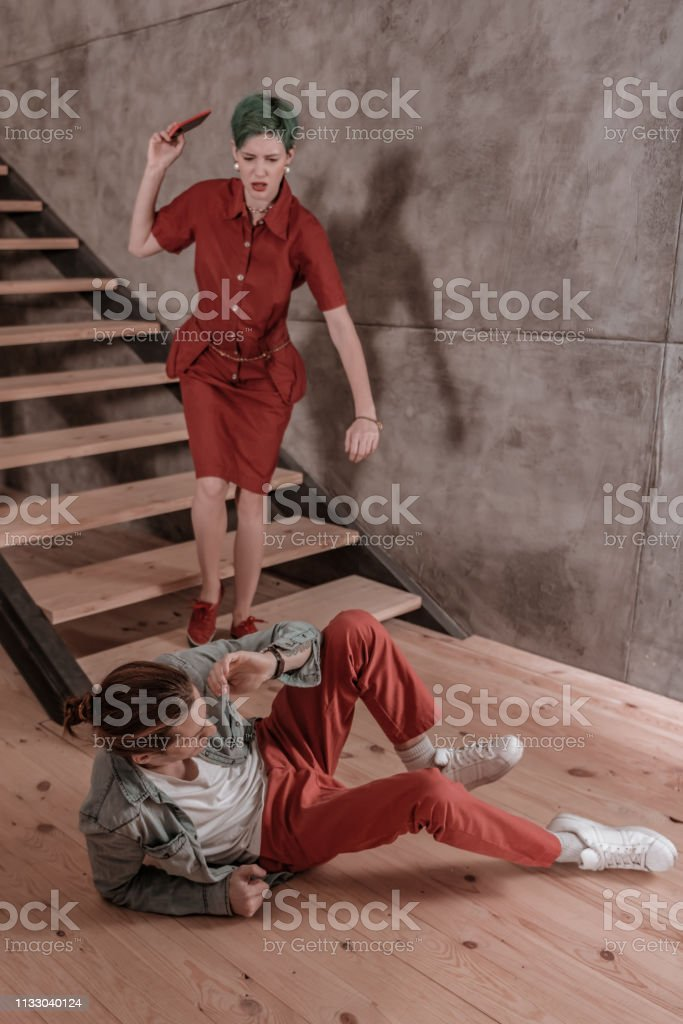 Man out. Angry green-haired girlfriend wearing red dress pushing man...