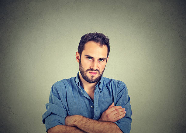 angry grumpy man, about to have nervous breakdown Closeup portrait of angry young man, about to have nervous breakdown, isolated on gray wall background. Negative human emotions facial expression feelings attitude anger stock pictures, royalty-free photos & images