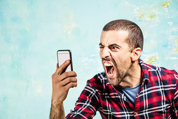 Angry guy shouting to someone in his smartphone stock photo