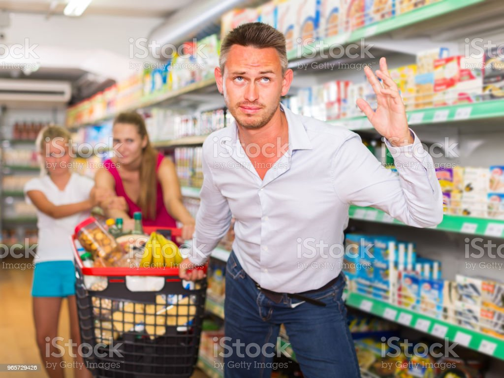 Angry husband pulls shopping cart from hands of his family  in shop - Royalty-free 1910-1919 Stock Photo