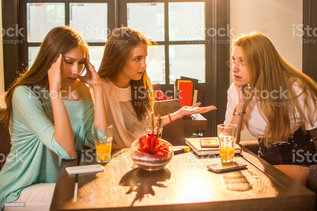 Angry, irritated teenage girlfriends arguing in cafe. stock photo