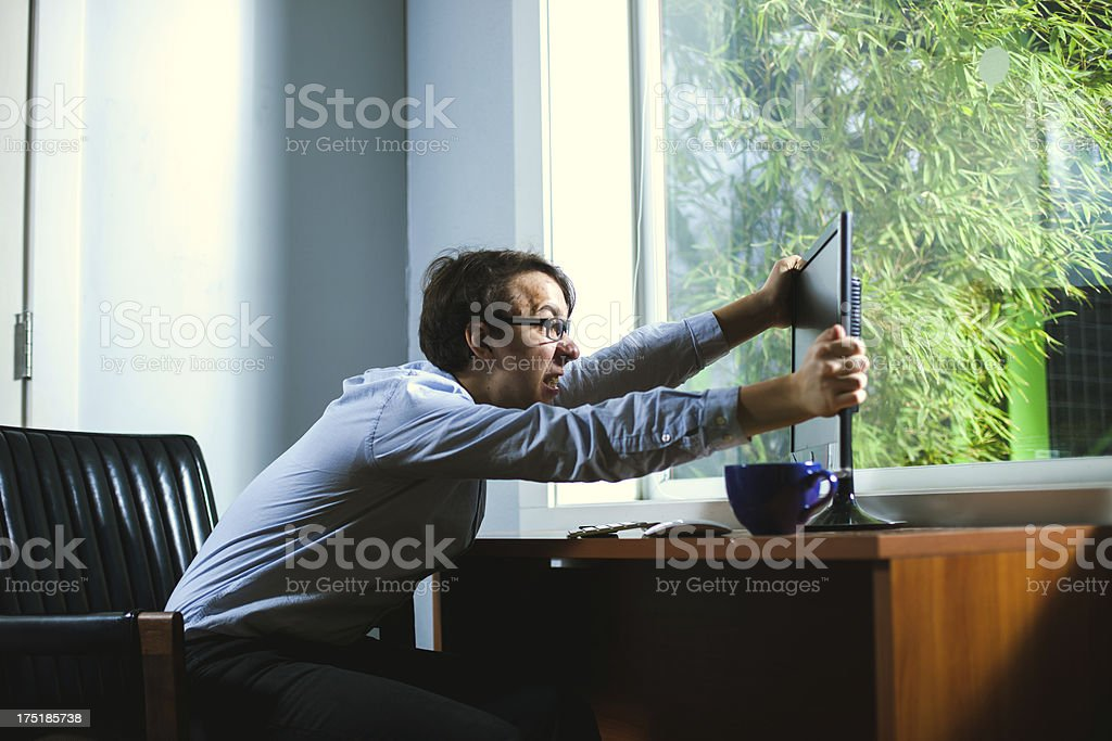 Angry IT Support Technician Shaking his Computer Violently stock photo