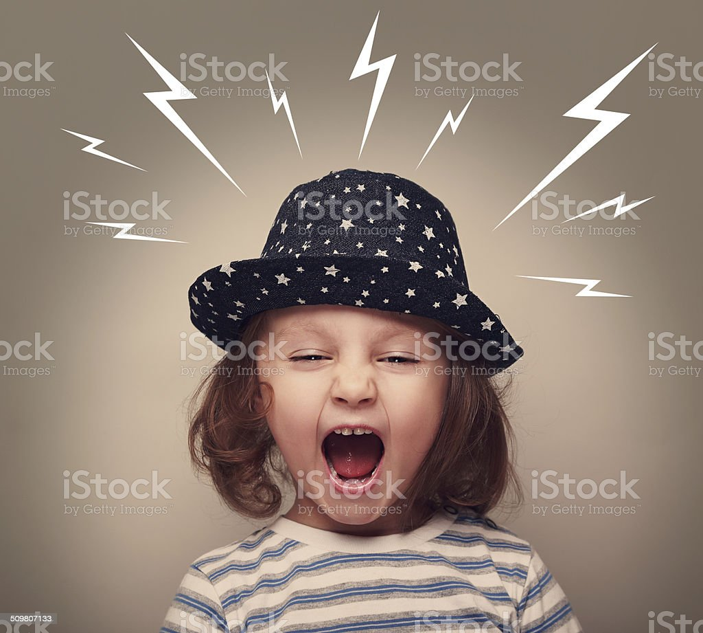 Angry kid in hat screaming white lightnings above on dark stock photo