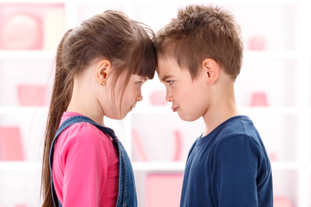 Angry kids looking at each other Angry kids after quarrel looking at each other brother stock pictures, royalty-free photos & images
