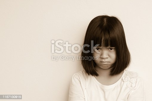 Angry little Asia kid in white shirt in cream wall background. Anger Asian student girl express her emotion on her face. Spoiled child does not get what she want. Disobedience Day