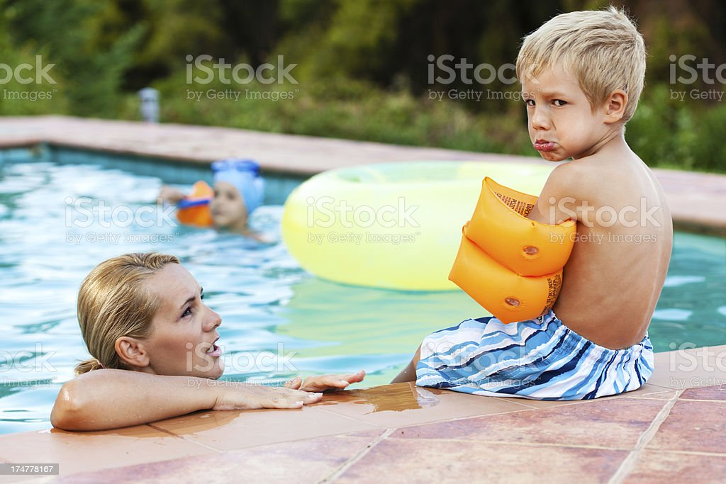 Angry little boy by the swimming pool stock photo