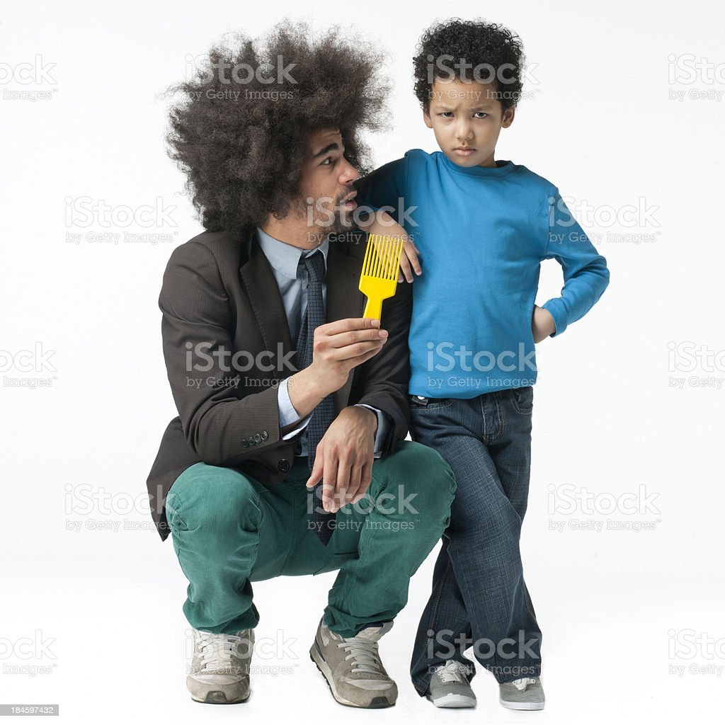 angry little boy leaning on shoulder of man holding comb stock photo