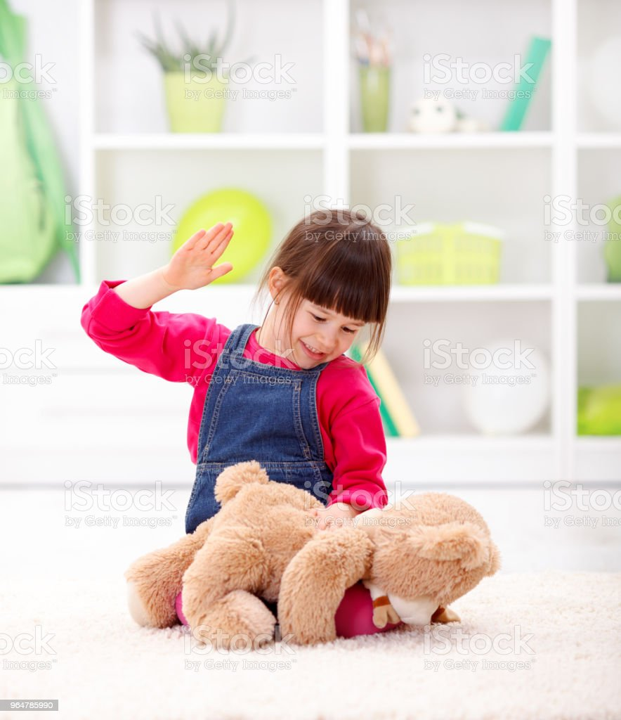 Angry little girl beating her teddy bear royalty-free stock photo