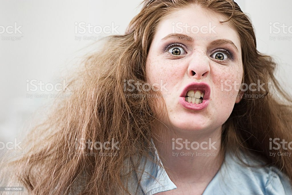 Angry looking young woman with gritted teeth stock photo