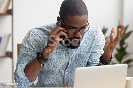 Angry mad african-american businessman talking on cellphone looking at laptop in office. Shocked manager received bad news discussing failing profit statistics with coworker, solving problem distantly