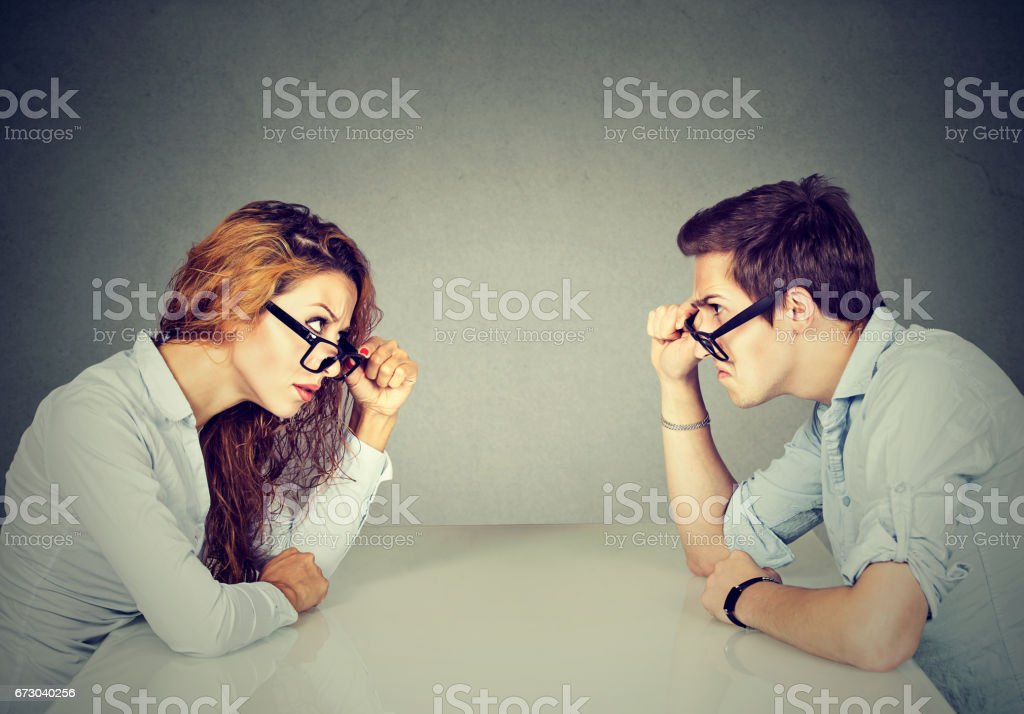 Angry man and woman sitting at table looking at each other with hatred and disgust stock photo