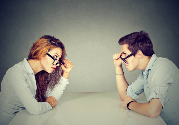 angry man and woman sitting at table looking at each other with hatred and disgust - imbalance stock photos and pictures