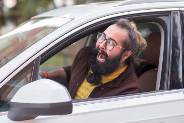 도 분노를 보여주는 바퀴 뒤에 화난 사람 - 악한 뉴스 사진 이미지