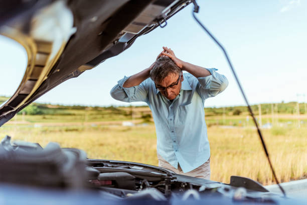 Angry man checking his car Senior Man examining a broken car on a sunny day. Photo of senior businessman looking under the hood of breakdown car at outdoor. Gray hair stressed man having trouble with his broken car looking in frustration on the failed engine. aground stock pictures, royalty-free photos & images