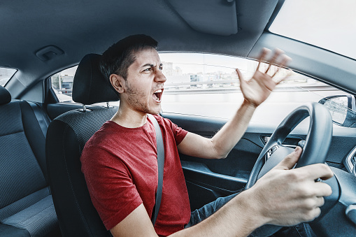 Angry man driver reacts aggressively to other road users. Concept of psychological problems, anger, and traffic accidents