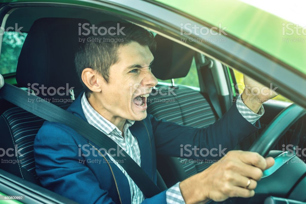 Angry man driver screaming in the car. Quarrel and dissatisfaction on the way. stock photo