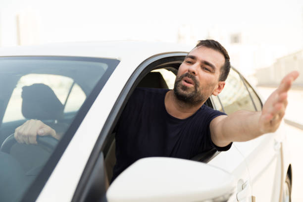 Angry man driving a vehicle is expressing his road rage. stock photo