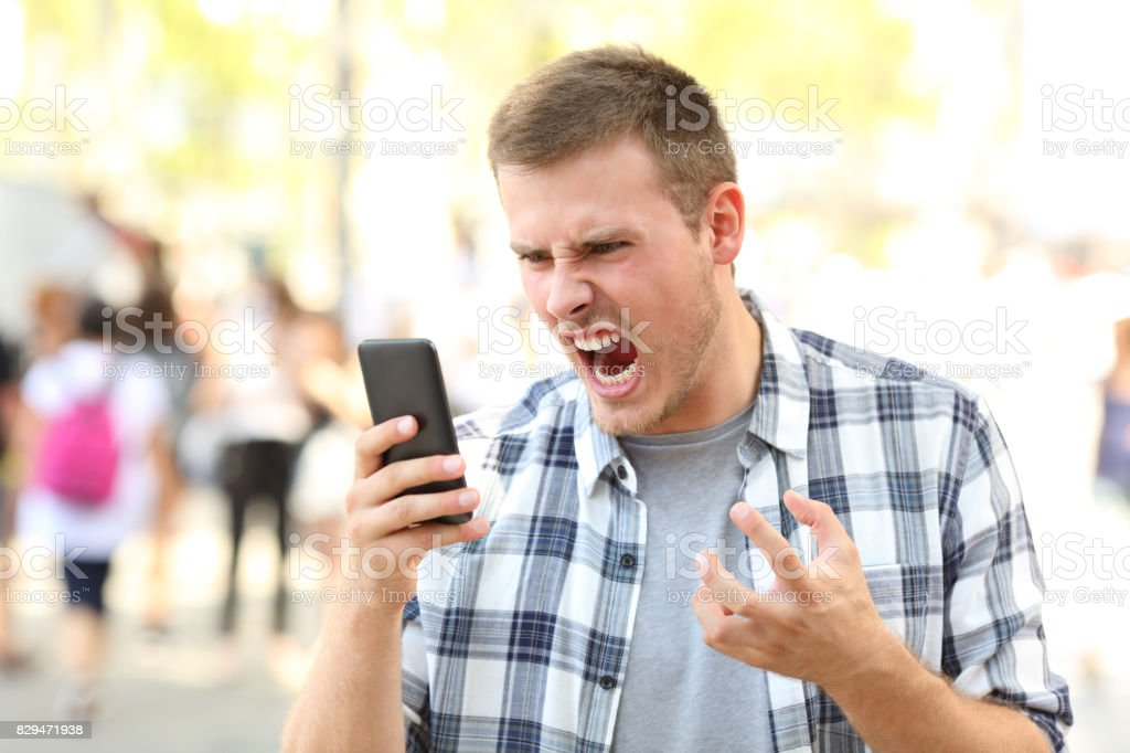 Angry man holding crashed phone stock photo