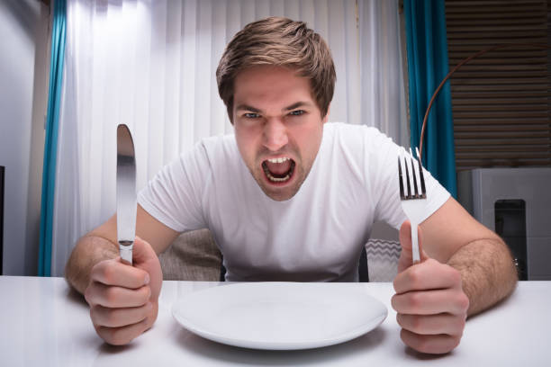 Angry Man Holding Knife And Fork Angry Man Holding Knife And Fork With Empty Plate On Table hungry stock pictures, royalty-free photos & images