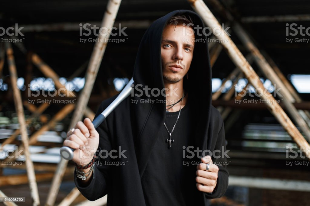 Angry man in black clothes holding a bat on the background of metal pipes stock photo