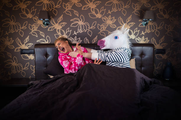 angry man in comical mask fighting with scared girlfriend in pajama on the bed - unicorn bed imagens e fotografias de stock