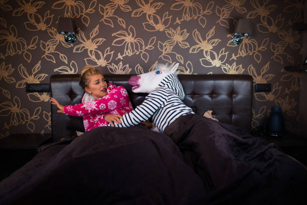 angry man in comical mask molest with scared young woman - unicorn bed imagens e fotografias de stock