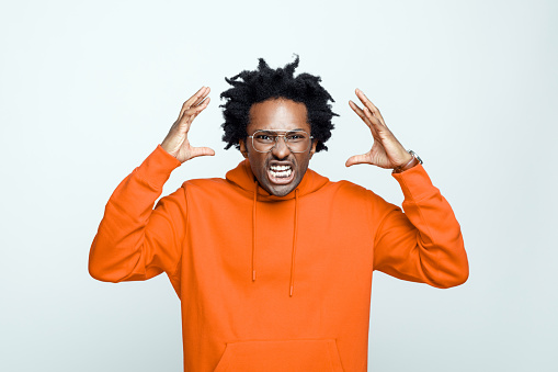 Furious afro american young man wearing orange hoodie and glasses, standing with raised hands and screaming at camera. Studio shot on grey background.