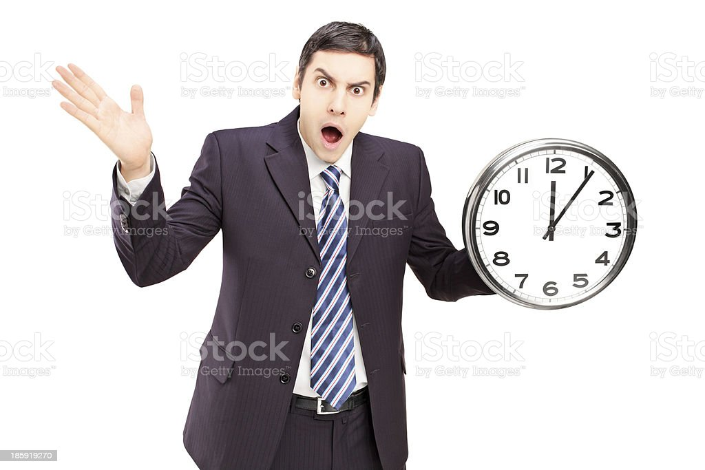 Angry man in suit holding a clock and gesturing royalty-free stock photo