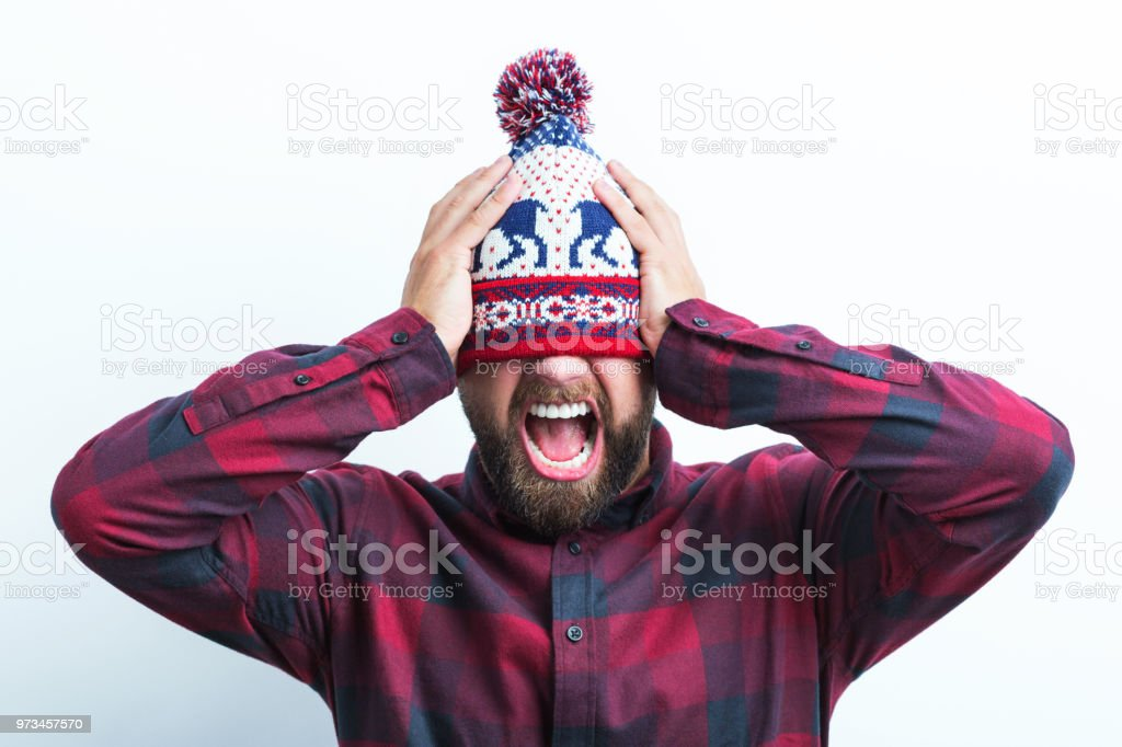 Angry man in winter cap Portrait of angry man wearing winter cap screaming on white background Adult Stock Photo