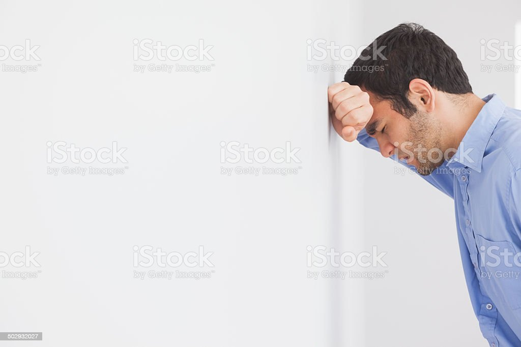 Angry man leaning his head against a wall stock photo