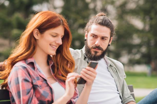 幸せな女テキスト メッセージングを見て怒っている人 - 羨望 ストックフォトと画像