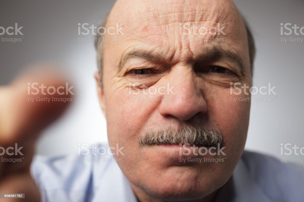 Angry man looking closely in photocamera stock photo