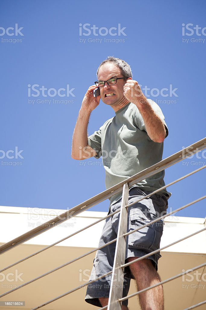 Angry Man On Balcony Shaking Fist While Using Mobile Phone royalty-free stock photo