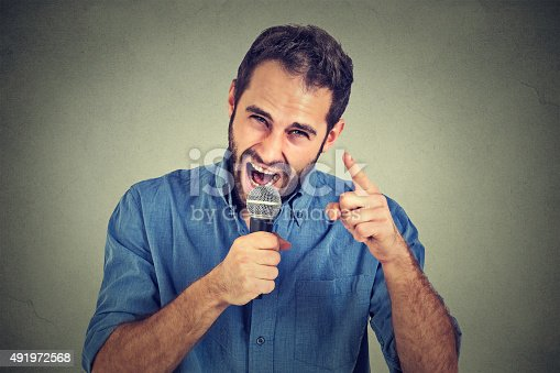 istock Angry man screaming in microphone 491972568