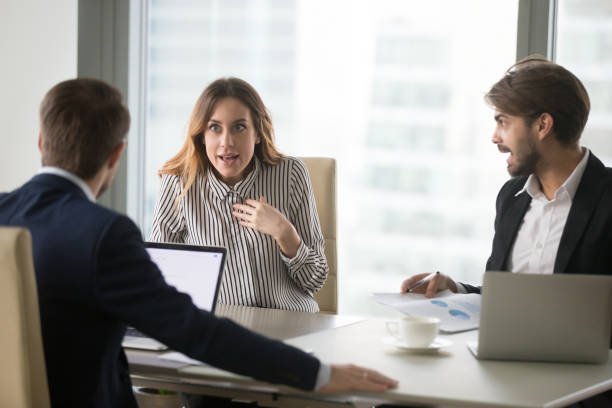 Angry man shouting at indignant female colleague. Angry man shouting at indignant shocked female colleague, blaming for mistake in front of boss. Disagreement, misunderstanding, bad negotiations, arguing, showing disrespect, gender discrimination. aggression stock pictures, royalty-free photos & images