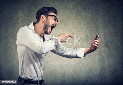 824614192 istock photo Angry man shouting at phone in hands 946965692