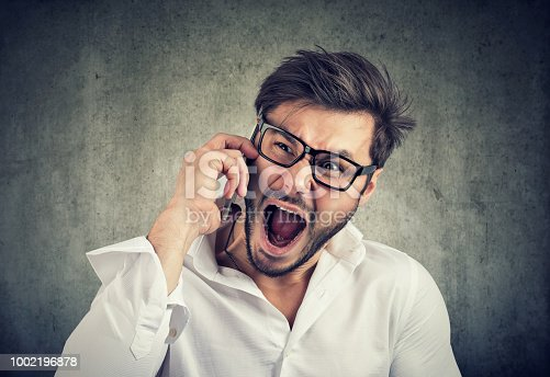 824614192 istock photo Angry man speaking on phone and yelling 1002196878