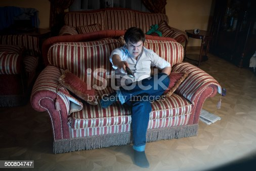 Portrait of angry man switching TV channel while sitting on sofa