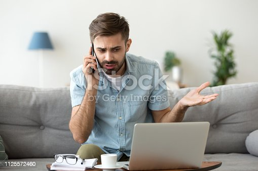 istock Angry man talking on phone disputing over computer laptop problem 1125572460