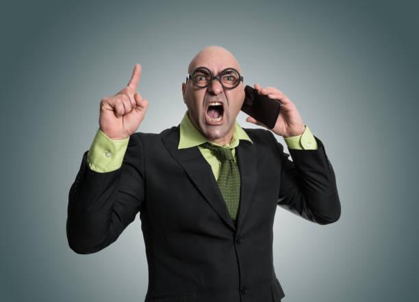 hombre enojado hablando por teléfono - studioimagen73 fotografías e imágenes de stock