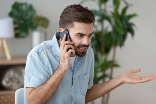 Angry man talking on smartphone solving work problem Angry man talk on smartphone arguing or solving problem, irritated male have cell phone conversation manage work trouble, annoyed guy use mobile call customer service disputing or complaining anger stock pictures, royalty-free photos & images