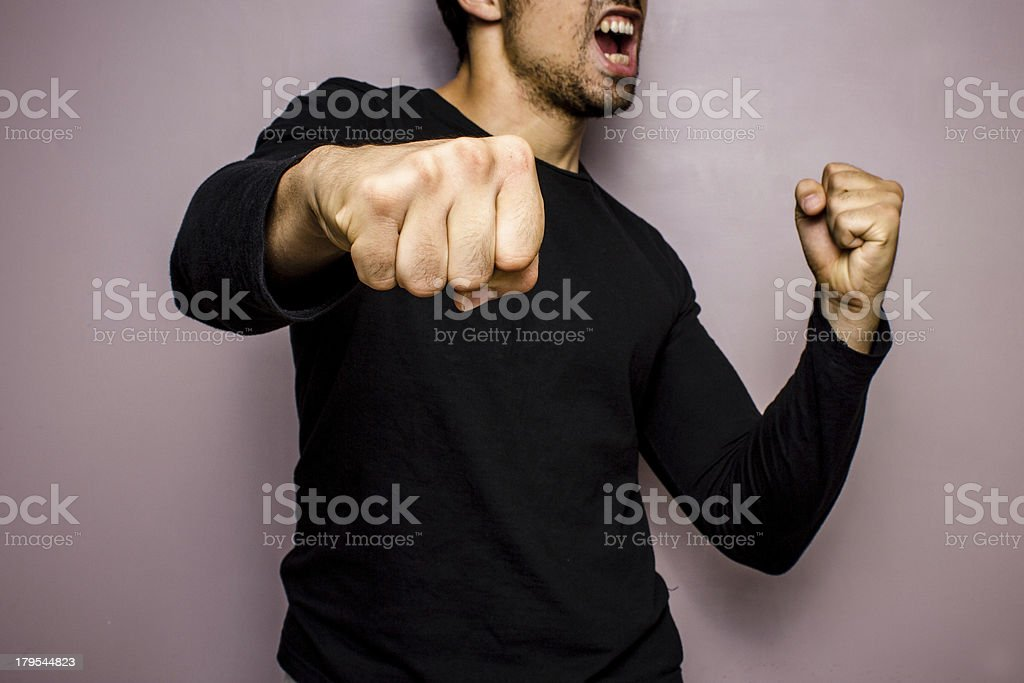 Angry man throwing a punch stock photo