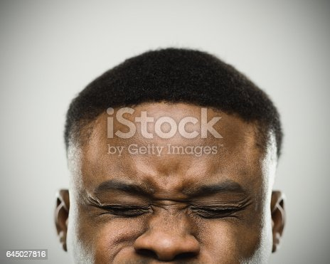 Close-up of angry real african man clenching eyes. Aggressive male is with eyes closed against gray background. Vertical studio photography from a DSLR camera. Sharp focus on eyes.