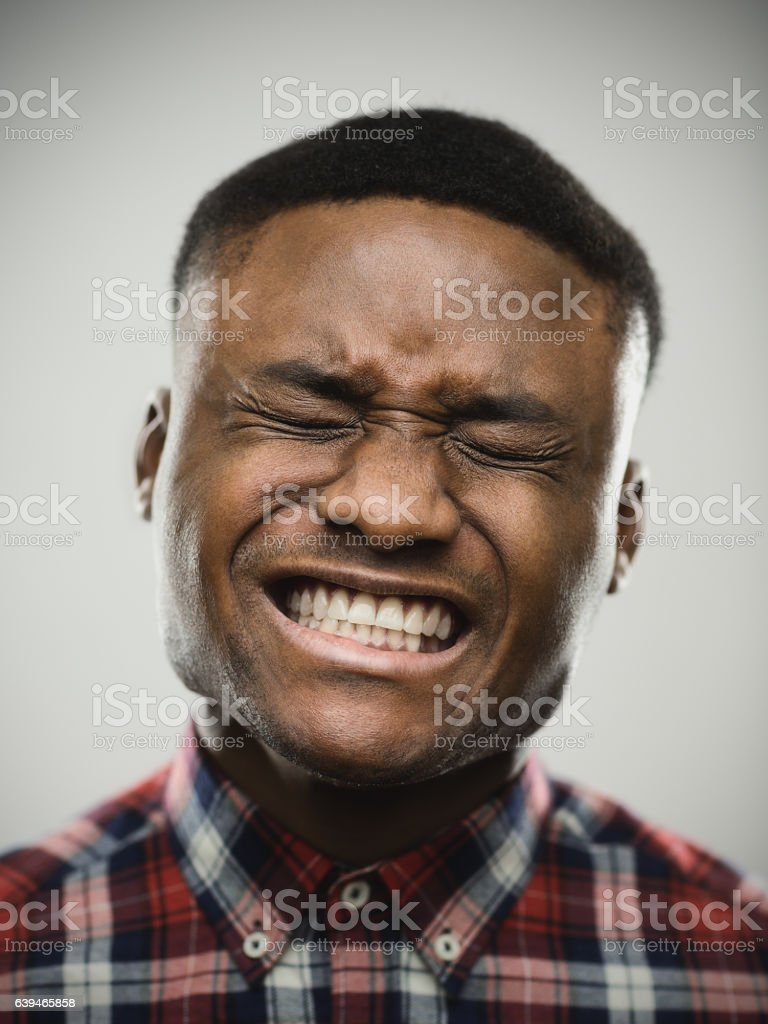 Angry man with eyes closed clenching teeth stock photo