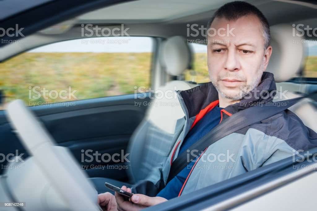 Angry man with phone while sitting inside his car