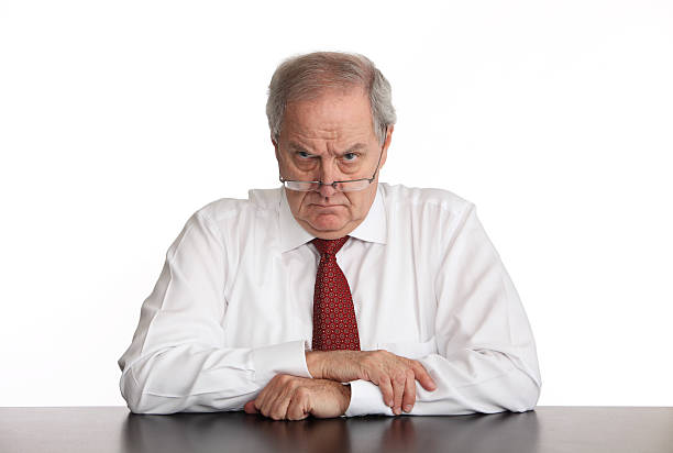Angry Manager Angry businessman sitting at his desk. foreman stock pictures, royalty-free photos & images